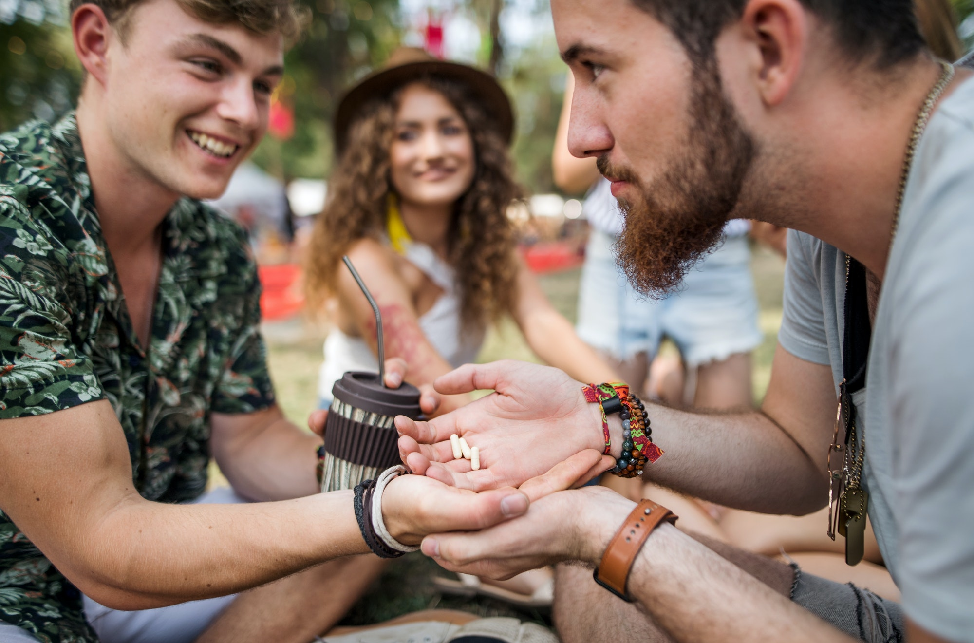 Group of young friends at summer festival, drug dealing concept